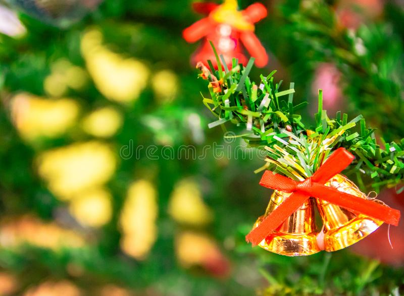Golden bells and red ribbon on Christmas tree on Christmas day, happy New Year concept, giving and celebration holiday. Golden bells and red ribbon on Christmas royalty free stock photo