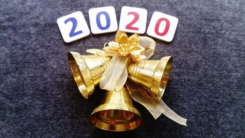 Golden bells with golden ribbons and flower. Above is written 2020. Dark velvety background. Happy New Year stock photos