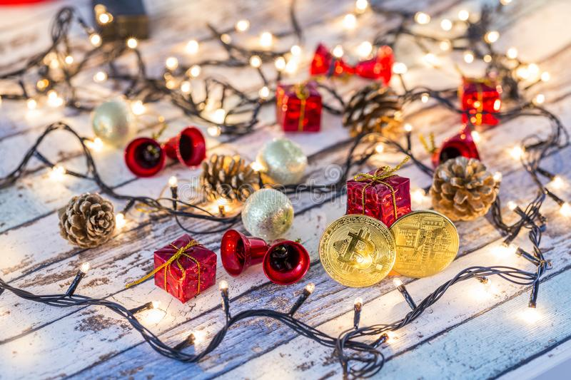 Golden bitcoin and another bitcoin in back with christmas decors stock photos