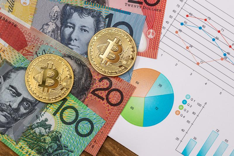 Golden bitcoin with Australian dollars. On graphs royalty free stock photography
