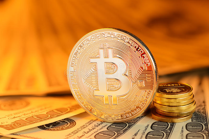 Golden Bitcoin and banknotes stock images