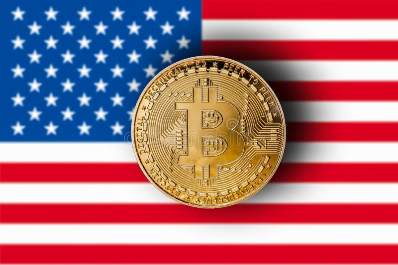 Golden bitcoin with blurred flag of the United States in the background/cryptocurrency concept.  stock photography