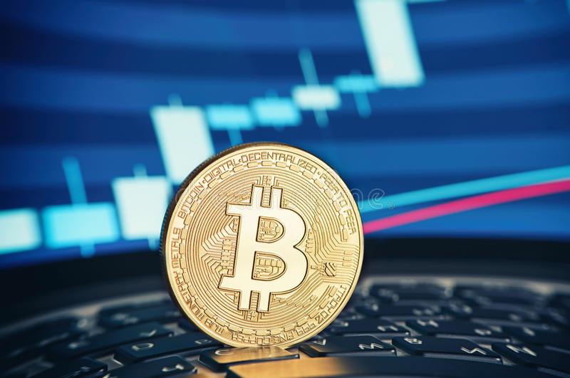 Golden Bitcoin coin on the laptop keyboard stock photography