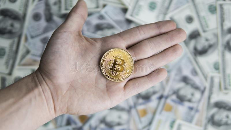 Golden Bitcoin coin on man`s hand on blurred us dollar bills background. Golden Bitcoins on US dollars in hand. Digital stock photo