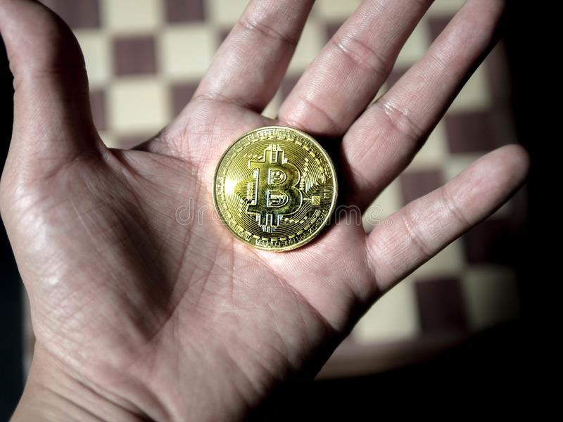 Golden Bitcoin coin on man`s hand on chess board background. Digital currency, Virtual money, Bussiness royalty free stock photo