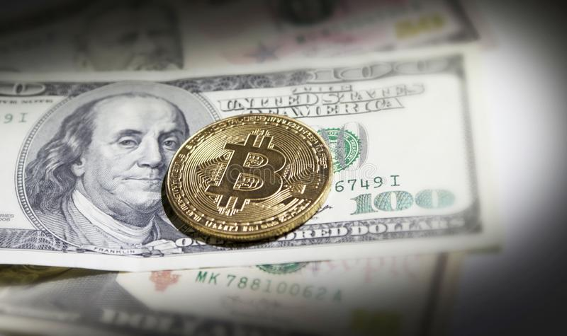 Golden bitcoin coin on us dollars close up. stock images