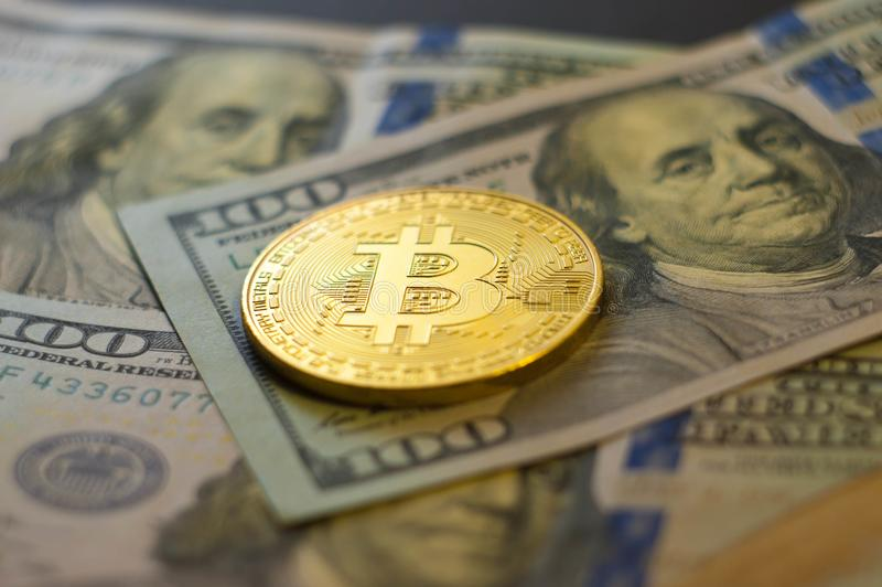 Golden bitcoin coin on us dollars close up royalty free stock photos