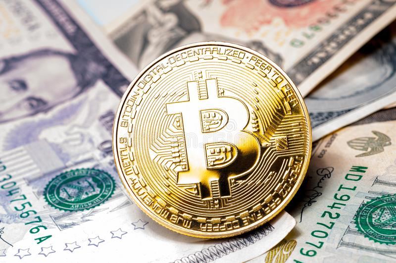Golden bitcoin coin on us dollars close up stock photos