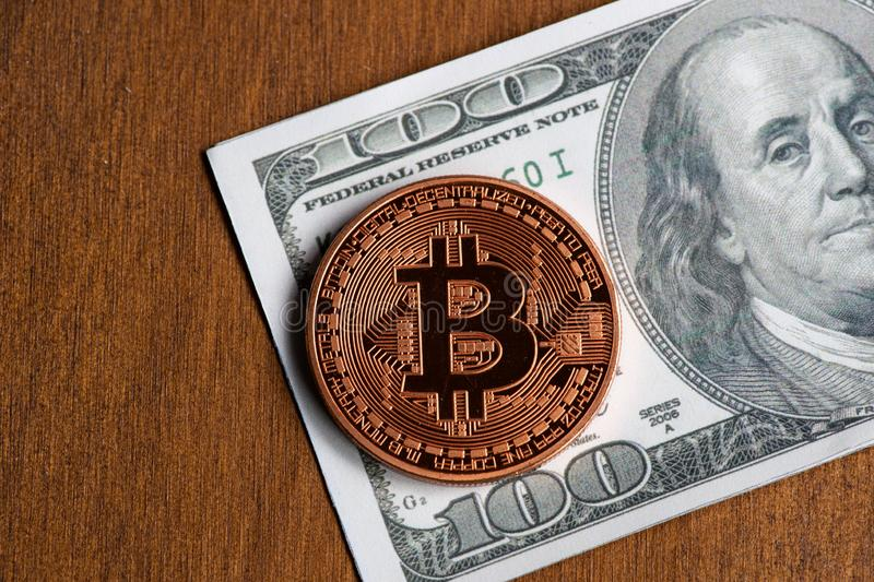 Golden bitcoin coin on us dollars close up royalty free stock images