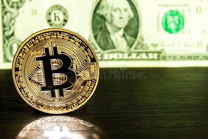 Golden Bitcoin coin on a us dollars close up. Bitcoin cryptocurrency. Crypto currency concept royalty free stock image