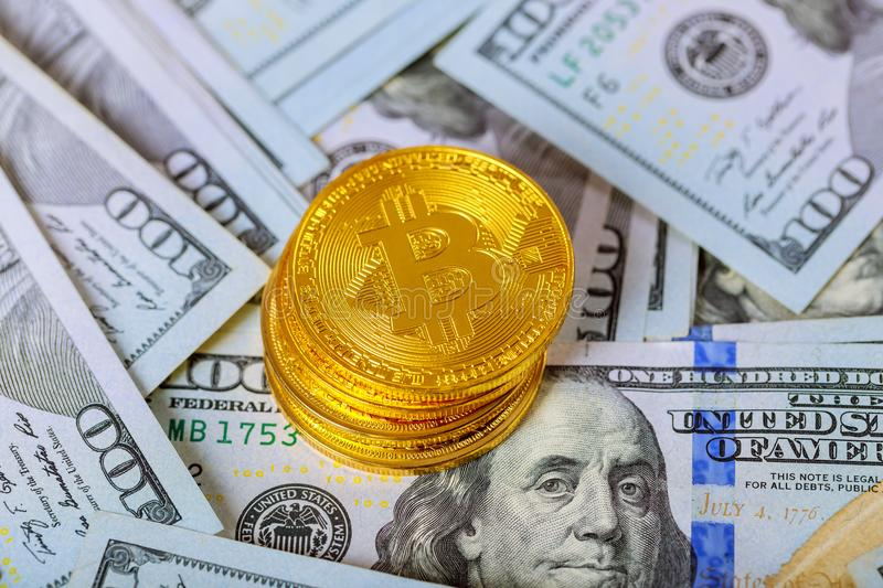 golden bitcoin coin on us dollars close up. Electronic crypto currency royalty free stock image