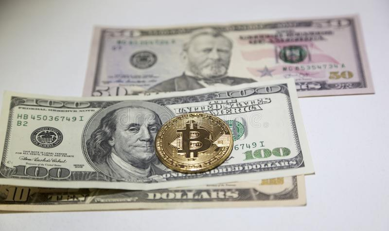 Golden bitcoin coin on us dollars close up. stock photography