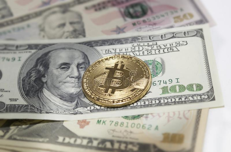 Golden bitcoin coin on us dollars close up. royalty free stock photo