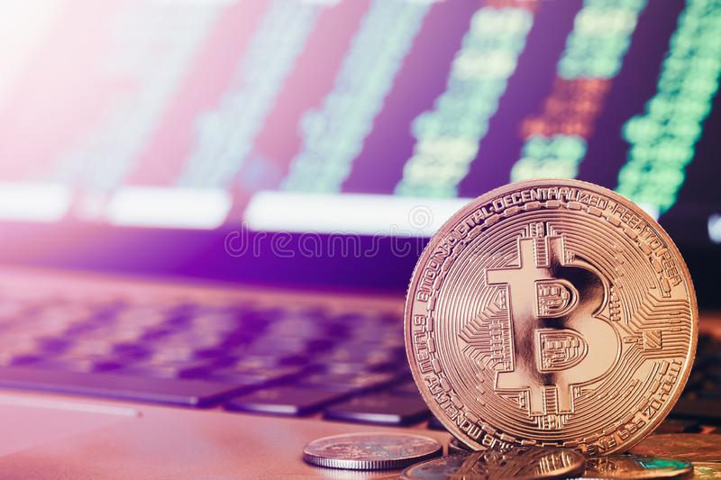 Golden Bitcoin coins in front of a green bullish cryptocurrency stock trading chart table. Bitcoin bullish trend stock trading stock image