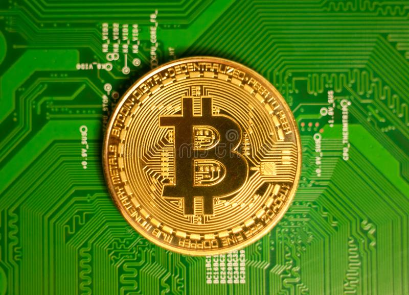 Golden Bitcoin Cryptocurrency on computer circuit board. Macro s stock photo