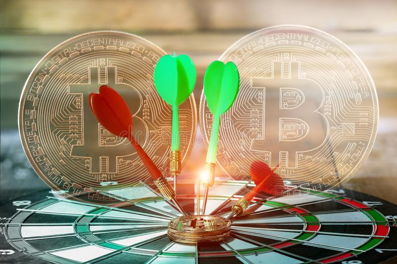 Golden Bitcoin on a dartboard dart, on the board center correct target on the game focuses. Golden Bitcoin on a dartboard dart, on the board center correct royalty free stock photo