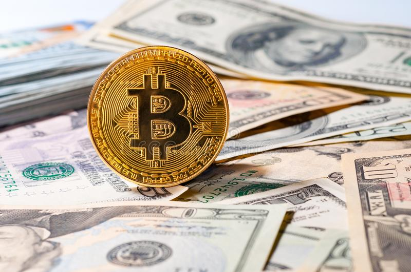 Golden bitcoin on different dollars background. stock photo