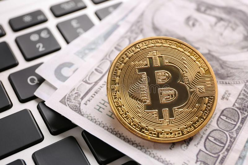 Golden bitcoin and dollar banknotes on PC keyboard stock photo