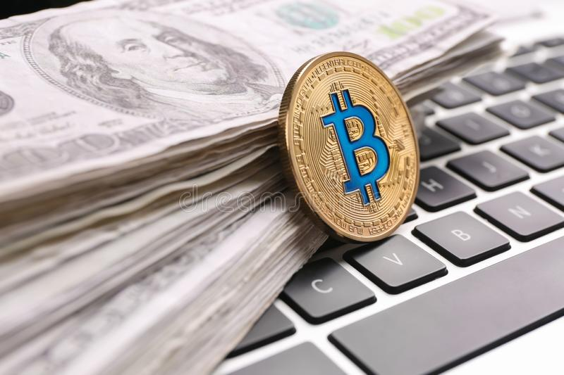 Golden bitcoin and dollar banknotes on PC keyboard royalty free stock photo