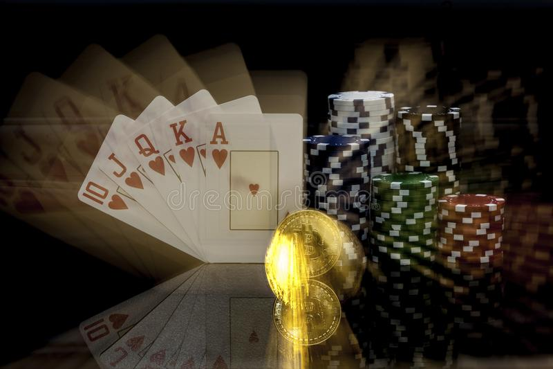 Golden Bitcoin in front of a royal flush stock image