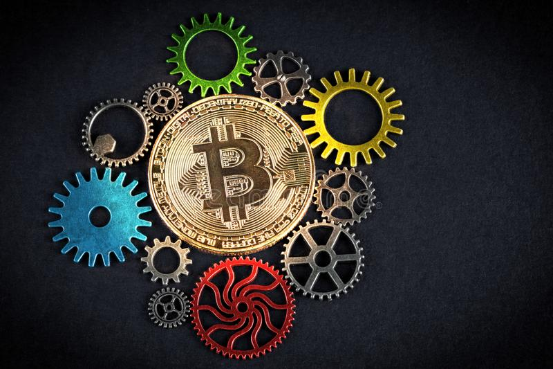 Golden bitcoin glowing among colorful cog wheels on black background with copy space. Cryptocurrency is the future - concept. stock photography