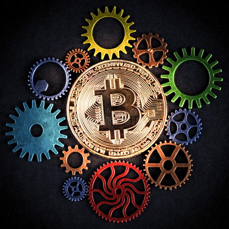 Golden bitcoin glowing among colorful cog wheels closeup, square format. Golden bitcoin glowing among colorful cog wheels closeup, square format royalty free stock images