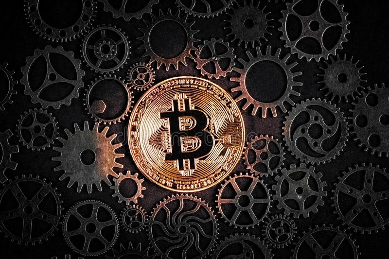 Golden bitcoin glowing in the middle of intricate cog wheels. Crypto currency concept. stock photography