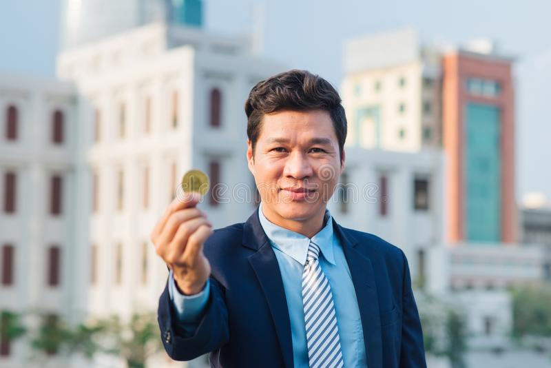 Golden bitcoin in hand of business man with black suit stock images