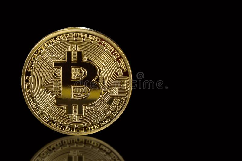 Golden bitcoin isolated on black background with reflection. Cryptocurrency mining concept. Free space for your text royalty free stock photos