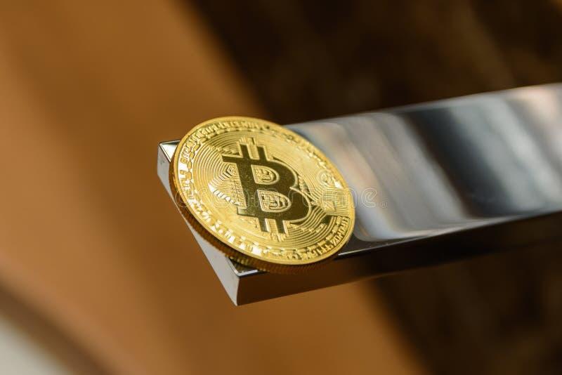 Golden bitcoin lie on metal water tap. Closeup stock photo