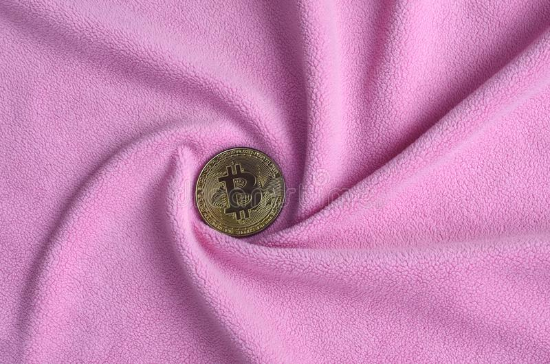 The golden bitcoin lies on a blanket made of soft and fluffy light pink fleece fabric with a large number of relief folds. The sha royalty free stock image