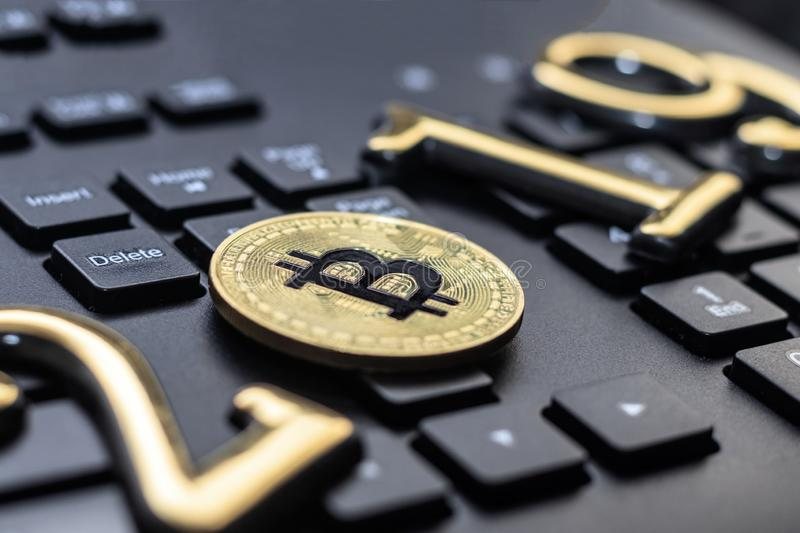 Golden bitcoin It lies on the keyboard of a dark color. The inscription 2019. There is a toning. Business currency laptop trade web bank cash electronic royalty free stock photo