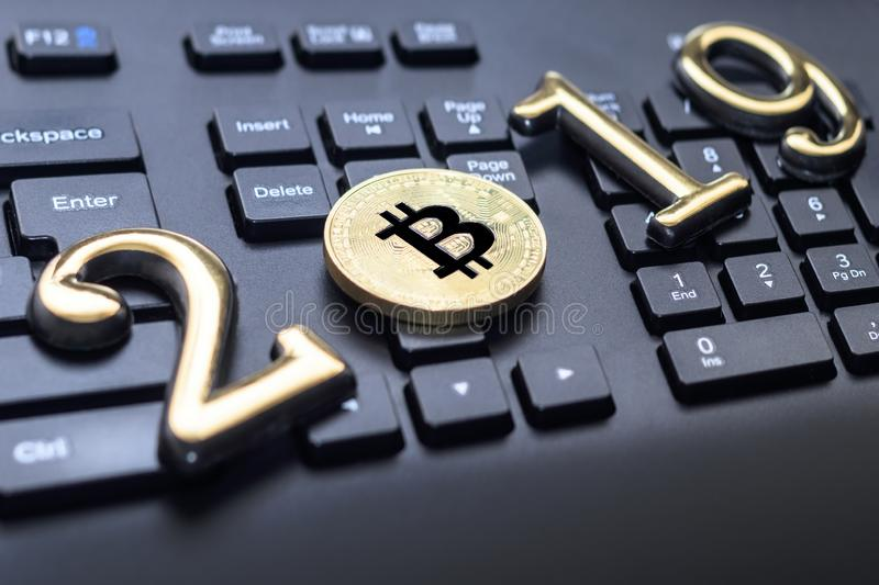 Golden bitcoin It lies on the keyboard of a dark color. The inscription 2019. There is a toning. Business currency laptop trade web bank cash electronic stock photo