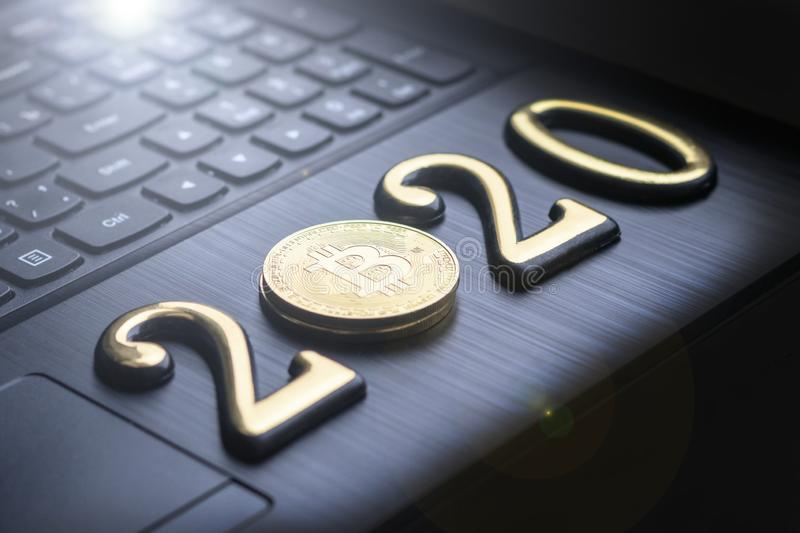 Golden bitcoin It lies on the keyboard of a dark color. The inscription 2020. There is a toning. Business currency laptop trade web bank cash electronic royalty free stock photos