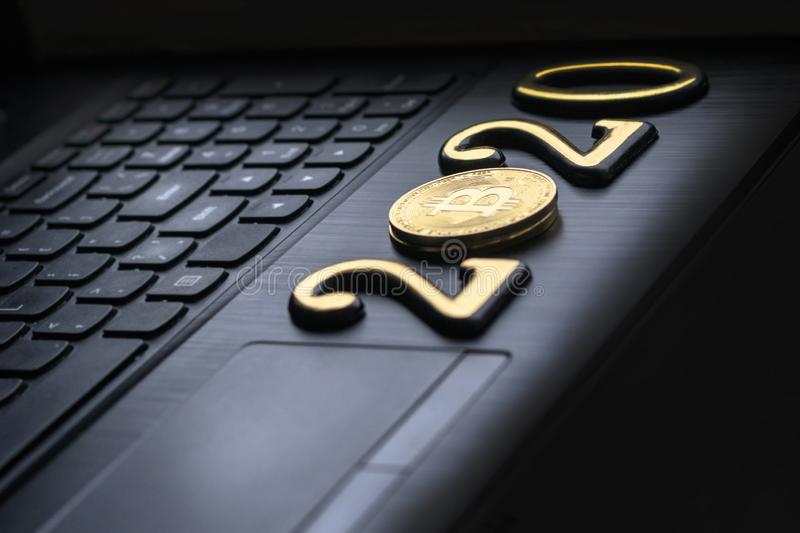 Golden bitcoin It lies on the keyboard of a dark color. The inscription 2020. There is a toning. Business currency laptop trade web bank cash electronic royalty free stock image