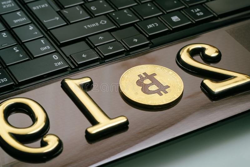 Golden bitcoin It lies on a laptop. The inscription 2019. There is a toning. Business currency keyboard trade web bank cash electronic financial mining money royalty free stock photos
