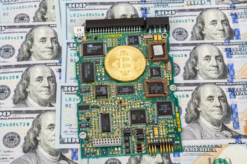 Golden bitcoin lying over electronic computer component with american dollars royalty free stock photos