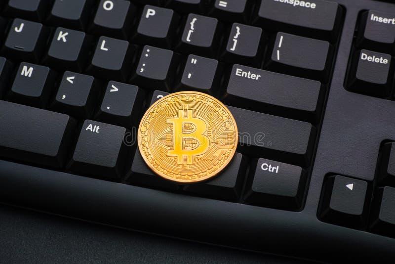 Golden bitcoin op een zwart computertoetsenbord royalty-vrije stock afbeeldingen