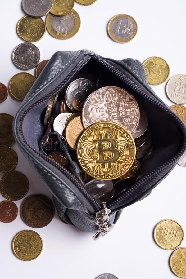 Golden bitcoin over  money coins  in wallet around international currency coins stock image
