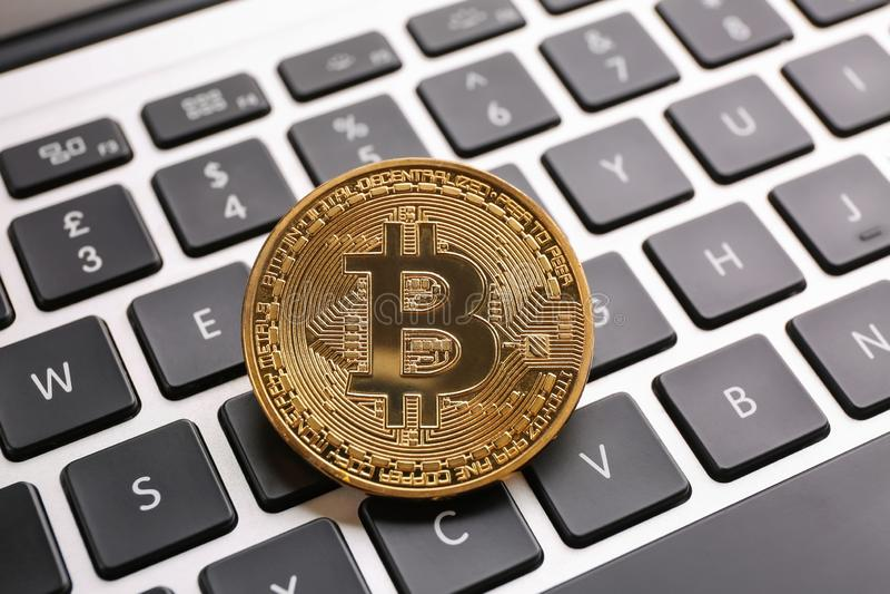 Golden bitcoin on PC keyboard stock photography