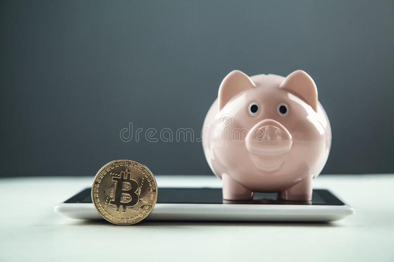 Golden Bitcoin with piggy bank on a digital tablet. Cryptocurrency investment concept stock photography