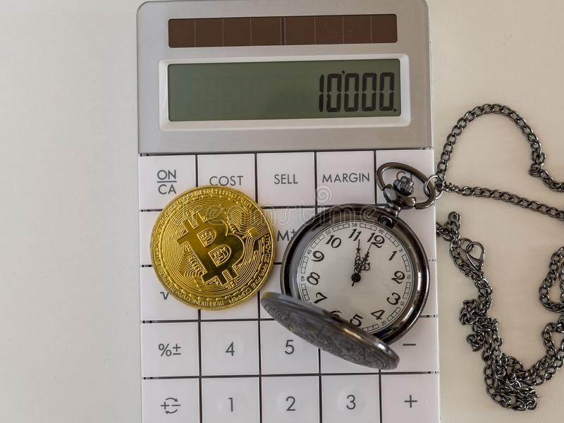 Golden bitcoin and pocket watch on calculator royalty free stock photo