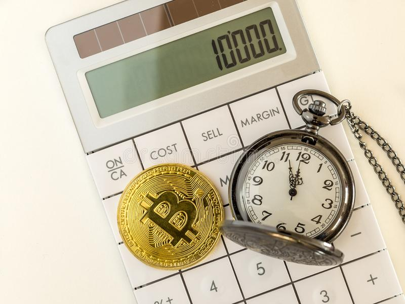 Golden bitcoin and pocket watch on calculator royalty free stock photography