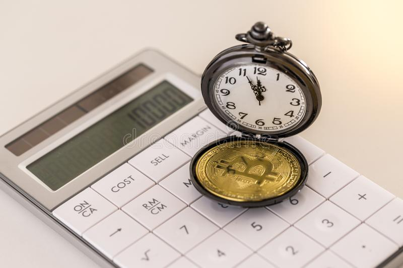 Golden bitcoin and pocket watch on white calculator stock photography