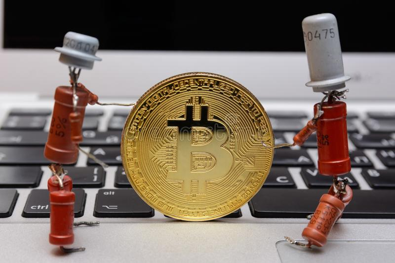Golden bitcoin stand on silver notebook keyboard stock image