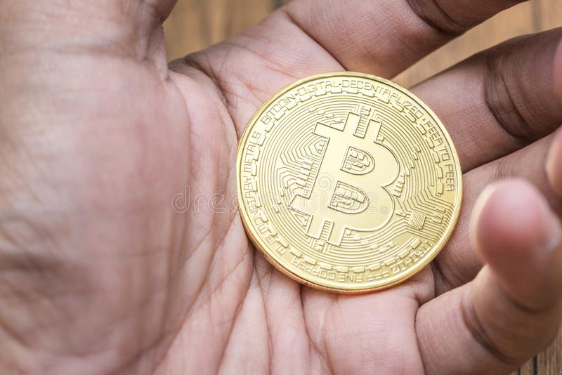 Golden bitcoin in the stock market investor hand for the digital money royalty free stock photography