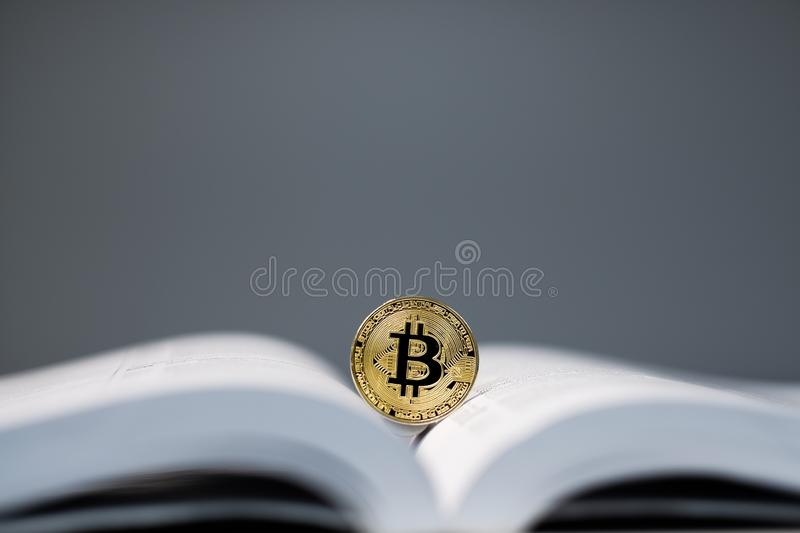 Golden bitcoin token on white textbook,bitcoin and education background concept stock photography