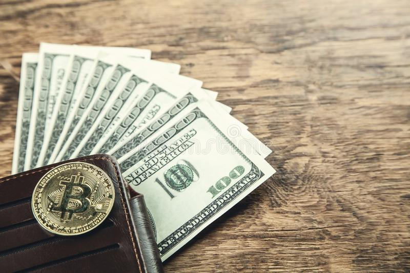 Golden Bitcoin with wallet and dollars on wooden background. stock photography