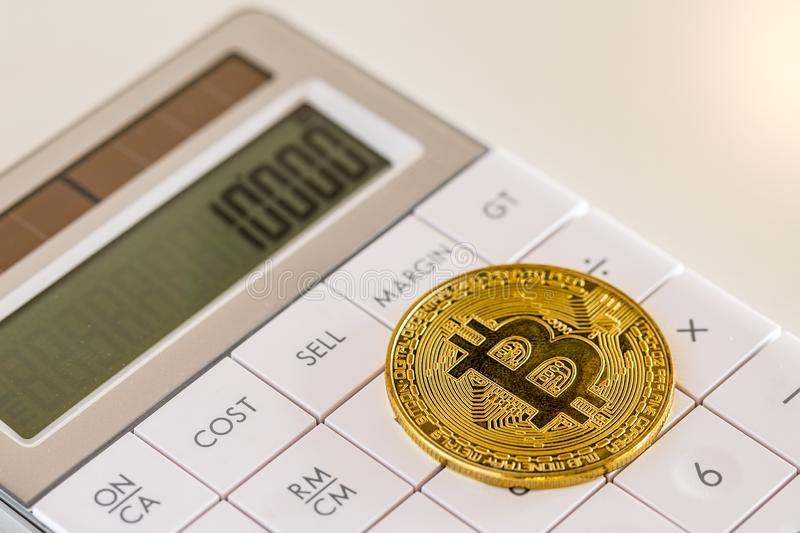 Golden bitcoin on white calculator close-up image royalty free stock photography