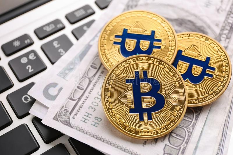 Golden bitcoins and dollar banknotes on PC keyboard royalty free stock photography